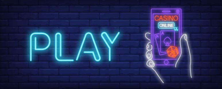 """Texten """"Play"""" brevid en hand som håller i en mobiltelefon med texten """"Casino online"""""""