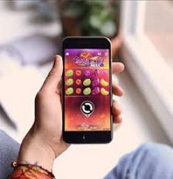 Hand håller smartphone med slotsspel